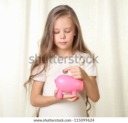 Little blond girl puts coin into piggy moneybox and dreaming about future purchase - stock photo