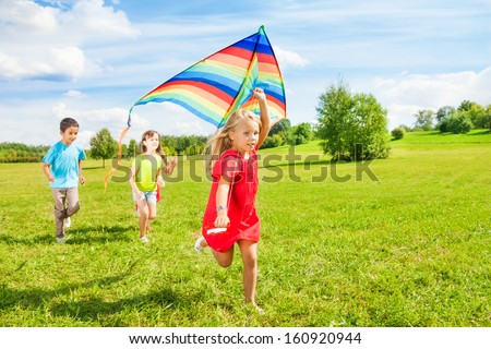 Little blond girl running in park with friends on sunny day - stock photo
