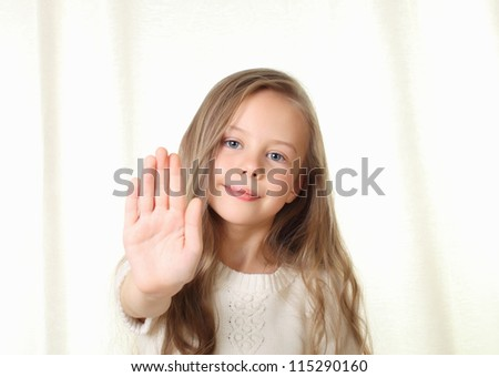 Little blond girl shows stop sign by palm an looking to camera - stock photo
