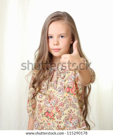 Little blond girl shows thumbs up - stock photo