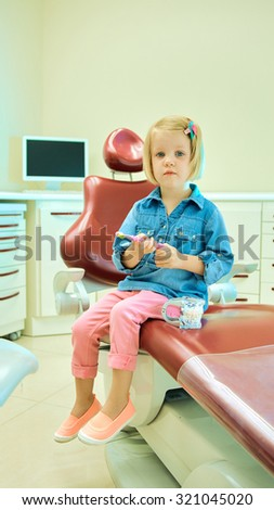 Little blond girl sitting in the dentists office - stock photo