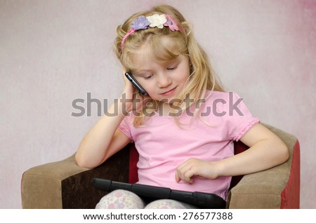 little blond girl speaking by mobile phone with tablet in hands - stock photo