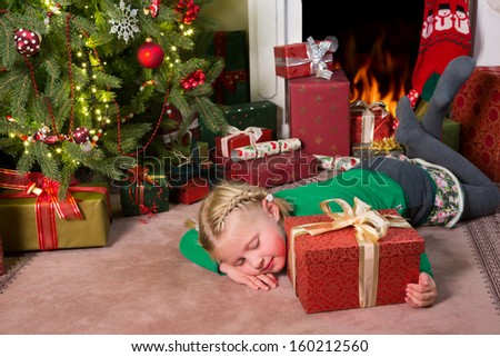 Little blond girl waiting in front of the christmas tree till she can open her present