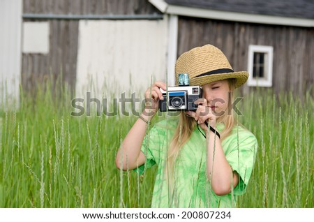 little blond girl wearing a hat and using an old-fashioned camera - stock photo
