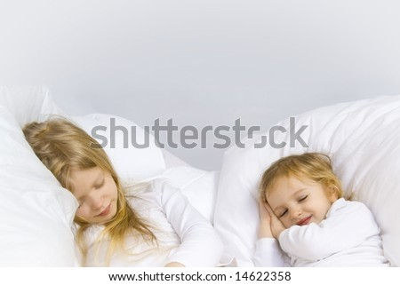 Little blond girl wearing white blouse in white bedchlothes