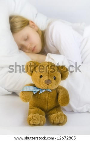 Little blond girl wearing white blouse in white bedclothes - stock photo