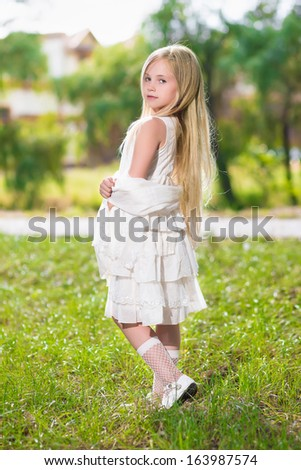 Little blond girl wearing white dress posing outdoors - stock photo