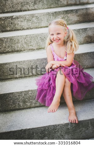 Little blond girl with a princess crown laughing, selective focus. - stock photo