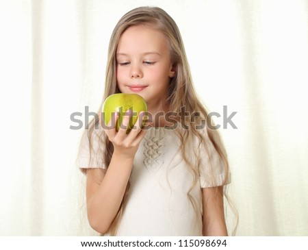 Little blond girl with apple looking on it and sniffing with appetite - stock photo