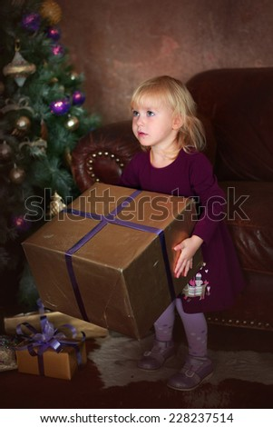 little blond girl with blue eyes at the decorated christmas tree with presents - stock photo