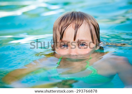 Little blond girl with blue eyes just emerged from the water in a pool. The pool is located in the courtyard of a house and the blue summer sky reflecting in water. - stock photo