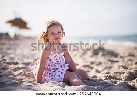 little blond girl with blue eyes on the beach near the sea dressed on white sun-dress with white flower in hair. Background diffused. Small lady play in the sand - stock photo