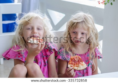 little blond girls sitting and eating pizza slice - stock photo