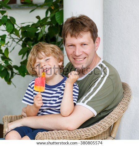 Little blond kid boy and young happy father eating together ice cream in summer. Funny family outdoors. - stock photo