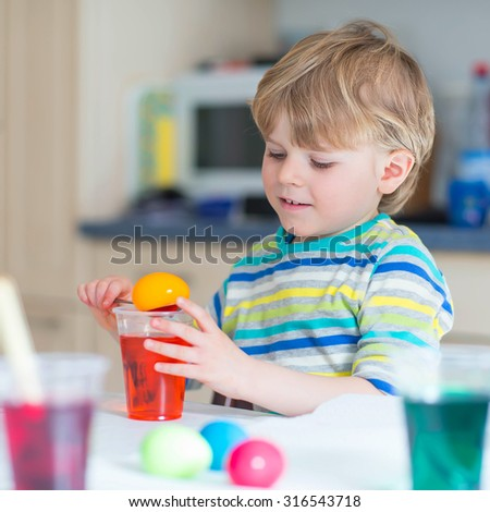 Little blond kid boy coloring eggs for Easter holiday in domestic kitchen, indoors. Child having fun and celebrating feast.