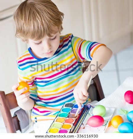 Little blond kid boy coloring eggs for Easter holiday in domestic kitchen, indoors. Child having fun and celebrating feast. - stock photo