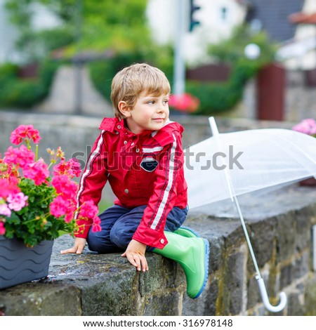 Little blond kid boy on way to school with big umbrella outdoors on rainy day. Child having fun and wearing colorful waterproof clothes