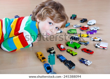 Little blond kid boy playing with lots of toy cars indoor. Toddler wearing colorful shirt and having fun. - stock photo