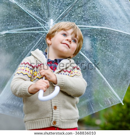 Little blond kid boy walking with big umbrella outdoors on rainy day. Child having fun and wearing colorful waterproof clothes and rain boots. - stock photo