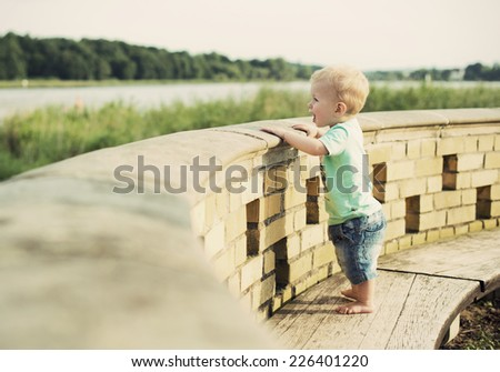 little blond one year old boy looks in the distance at a lake promenade at summer, vintage style  - stock photo