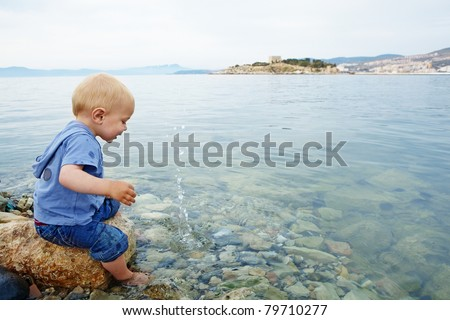 Little blond one year old boy sitting on a rock with his feet in the sea water on a warm summer evening and watching stones make splashes, in a resort town in Turkey - stock photo