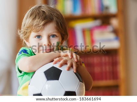 Little blond preschool boy of 4 years with football watching soccer world cup game 2014 on tv - stock photo