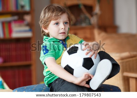 Little blond preschool boy of 4 years with football watching soccer world  cup 2014 in Brazil  on tv