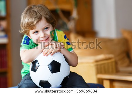 Little blond preschool boy of 4 years with football watching soccer world cup on tv - stock photo