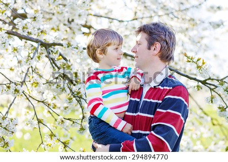Little blond preschool child and young father hugging in blooming cherry garden in spring. Happy family celebrating father's day. - stock photo