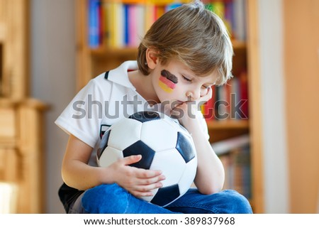 Little blond preschool kid boy with ball watching soccer european cup game on tv. Sad child about lost game of his football team. Champions league concept.