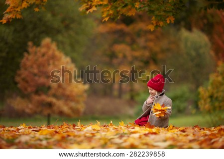 little blond smiling girl in the grey coat, red hat and red dress sitting on the ground in the autumn park and holding yellow leafs in her hands