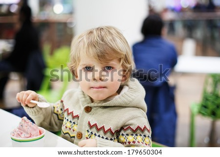 Little blond toddler boy eating ice cream iin shopping mall, indoor