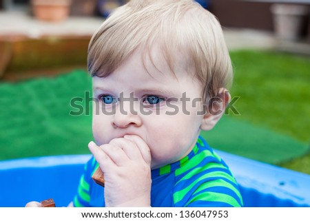 Little blond toddler boy of one year playing with water in summer garden