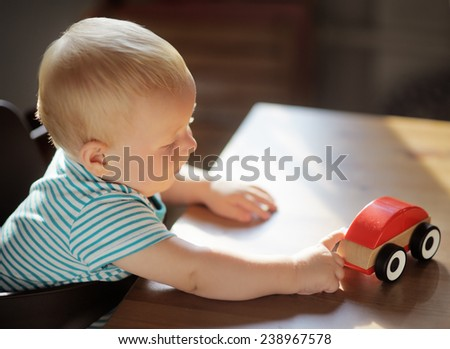 Little blond toddler boy playing with toy car  - stock photo