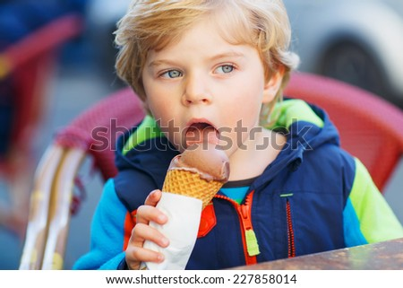 Little blond toddler child eating chocolate ice cream.