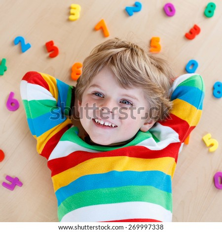 Little blond toddler child playing with lots of colorful plastic digits or numbers, indoor. Kid boy wearing colorful shirt and having fun with learning math - stock photo