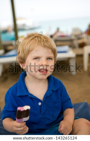 Little blond toddler eating chocolate ice cream, outdoors