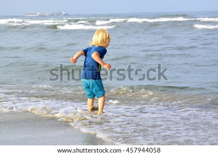 Little Blonde Boy Playing On The Beach