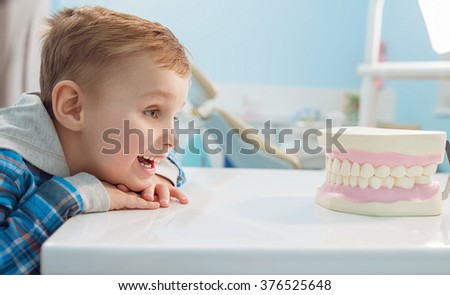 little blonde boy smiling and looking directly into the jaw in dental clinic.  - stock photo