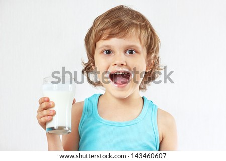 Little blonde boy with a glass of fresh milk on white background