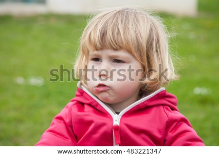 little blonde cute child red jacket sitting looking and chewing food with green grass background