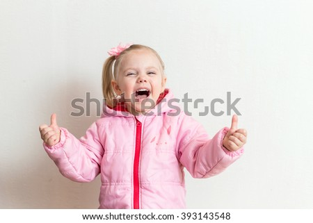 "little blonde girl in a pink jacket with a tail side four years shows the ""cool"" and laughs  white background horizontal photo"