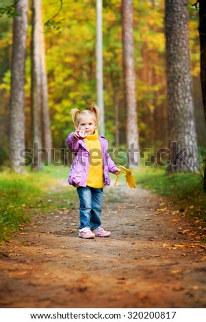 little blonde girl in a skirt tutu standing in tall grass looking