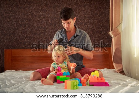little blonde girl in colourful dress plays toy constructor and father brushes her hair sitting on white bed