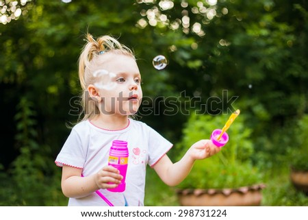 little blonde girl inflates soap bubbles on a summer day outdoors - stock photo