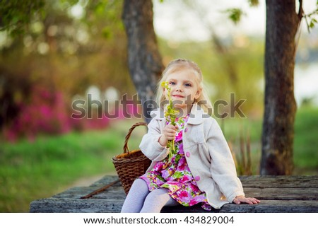 little blonde girl is four years with a basket of summer in the rays of the setting sun, against the backdrop of pink flowers