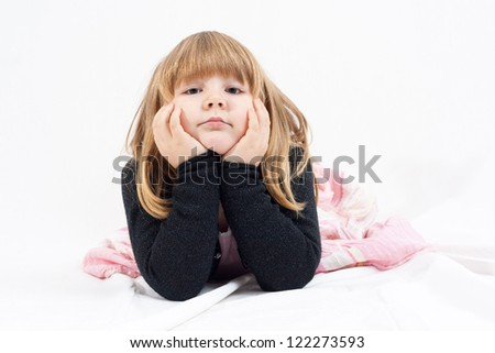 little blonde girl lie on a white blanket and looking bored into camera