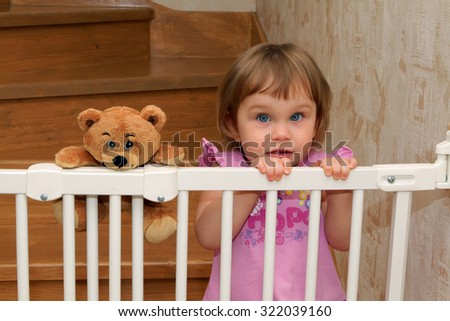 Little blonde girl on the stairs with a gate with a teddy bear friend - stock photo