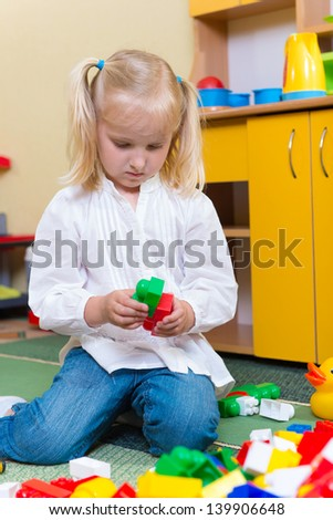 Little blonde girl playing with building bricks in preschool sitting on floor - stock photo
