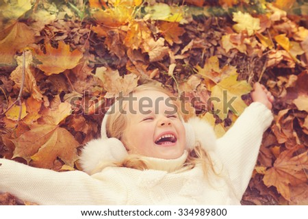Little blonde girl portrait lying on autumn yellow maple leaves outstretched hands and smiling, play outdoor in autumn park, happy childhood. - stock photo